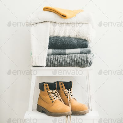 Pile of warm sweaters, blankets, cap and boots, square crop