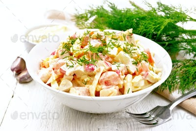 Salad of surimi and eggs with mayonnaise on wooden board