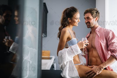 Beautiful young passionate couple is smiling while hugging in kitchen at home