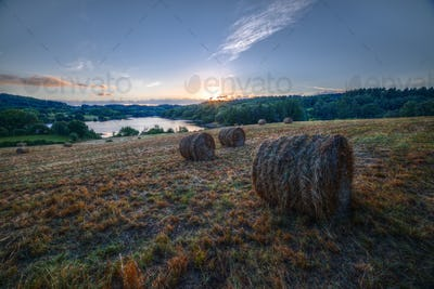 Sunset in a field with bales of grass