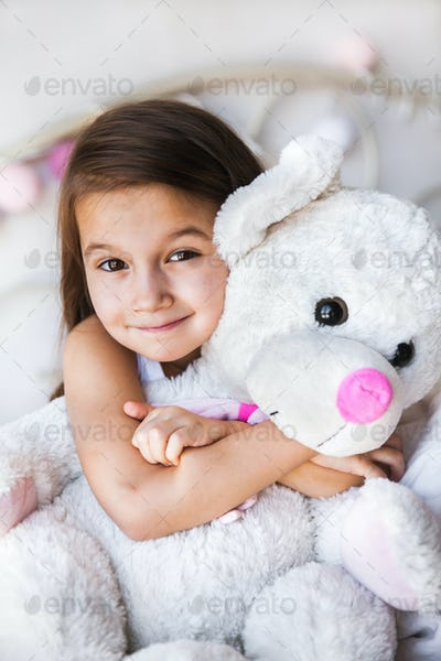 Little girl with her teddy sitting on the bed. home, comfort, family, relationships, people