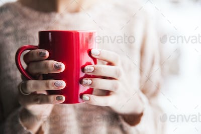 Woman's hand holding a red cup of coffee. With a beautiful winter manicure. Drink, fashion