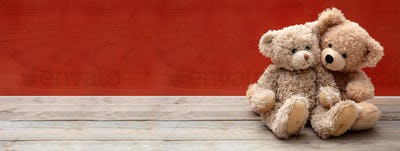 Love, friendship concept, tight hug. Teddy bears couple on wooden floor, red wall background