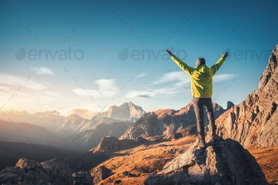 Sporty man standing on the stone with raised up arms