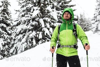 Winter hike in white snowy woods, man hiking