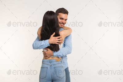 Handsome man hugging his girlfriend on white background