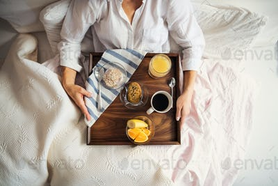 A midsection of woman with breakfast in bed in the morning, using smartphone. A top view.