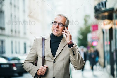 Mature businessman standing on a street in city, using smartphone.