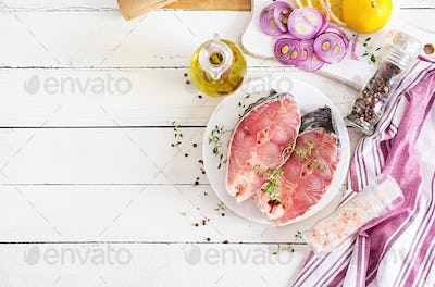 Raw steak of carp fish with lemon and thyme  on white wooden background.