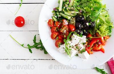 Greek salad of fresh cucumber, tomato, sweet pepper, lettuce, onion, feta cheese and black olives