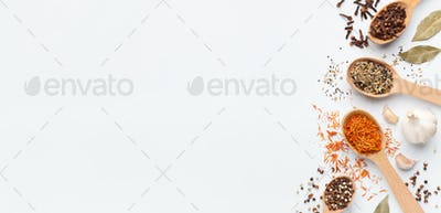 Various spices spoons and herbs on white background