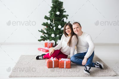 Holidays and people concept - Young couple with Christmas present on a Christmas morning