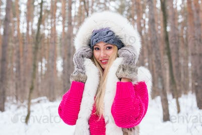Winter, beauty and fashion concept - Portrait of blond young woman in fur coat at snowy nature