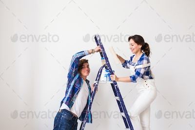 Family, renovation, happiness and redecoration concept - young family doing repair, painting walls