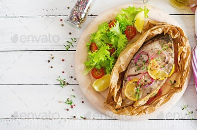 White fish steak (carp) baked in parchment paper with vegetables. Fish dish. Top view