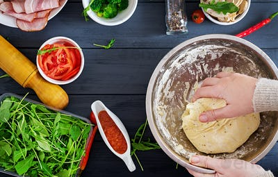 Italian pizza. Hands working with dough preparation pizza or pie making ingredients on table.