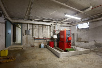 Basement with red heating boiler in old house interior