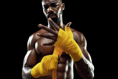 Afro American boxer is wrapping hands with bandage