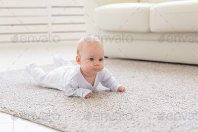 Family, childhood concept - Close up portrait of pretty baby lie on the floor