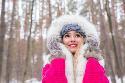 Fashion, winter and people concept - Young attractive woman dressed in fur waistcoat over snowy