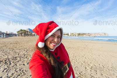 People, holidays and christmas concept - young woman in santa costume taking selfie on beach