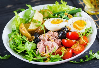 Healthy hearty salad of tuna, green beans, tomatoes, eggs, potatoes, black olives