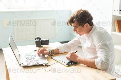 Business, technology, people concept - handsome man working with graphic tablet. He is an