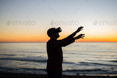 Young man using virtual reality glasses on over beautiful sky background