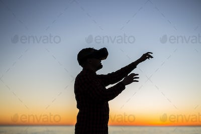 Young man wearing virtual reality goggles on sky background dreams come true