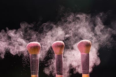 Make up, beauty and mineral cosmetic concept - Cosmetics brush and explosion light pink colorful