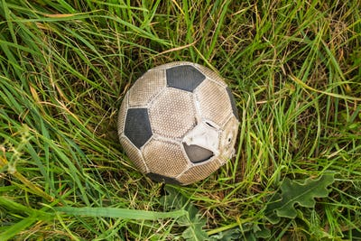 Old Soccer ball on the green grass, top view