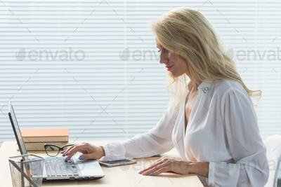 Technology, business and people concept - Beautiful woman in glasses working at the computer