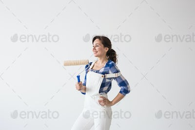 Redecoration, renovation, new home and people concept - young attractive brunette woman doing repair