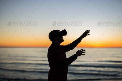 Man using virtual reality glasses on over beautiful sky and sea background