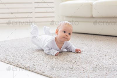 Childhood, babyhood and people concept - little baby boy or girl crawling on floor at home