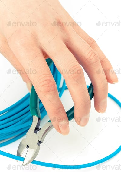 Hand with nippers and blue cable on white background, electrical engineering concept