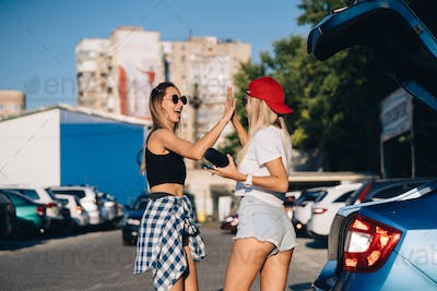 Two young girls in sunglasses posing for the camera on the car parking