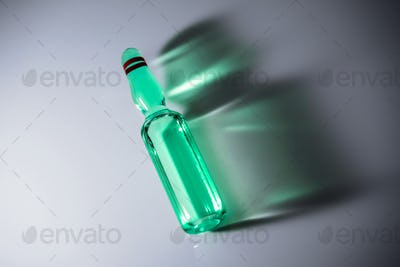 Vial detail with yellow medication, isolated side shadow on white background