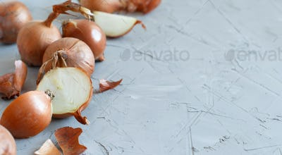 Yellow onions on a grey board