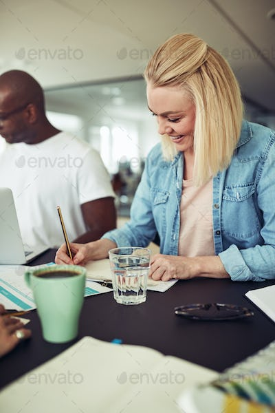 Smiling businesswoman working with a colleague at an office table