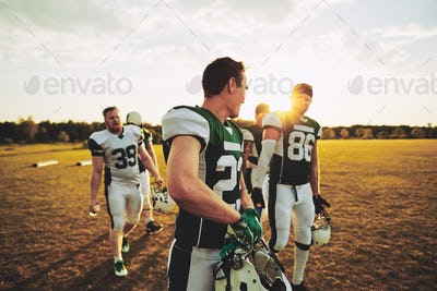 American football teammates walking off a sports field after practice