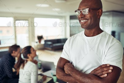 Smiling African businessman standing confidently in an office