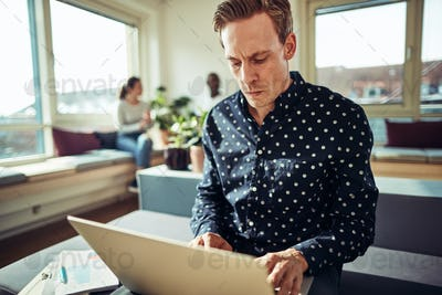 Focused young businessman using a laptop at his office desk