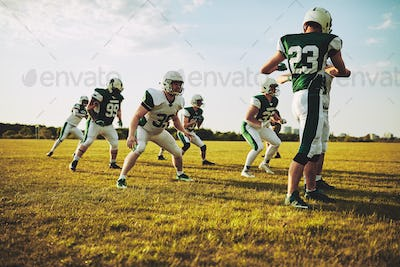Football players doing defensive drills during a practice session outdoors