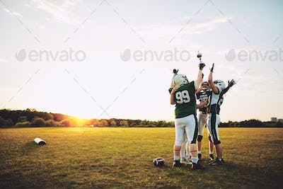 Football team celebrating with their championship trophy on a field