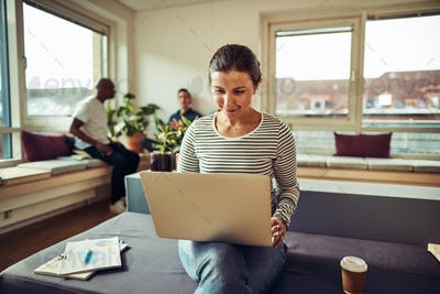 Smiling young businesswoman working online with colleagues in the background