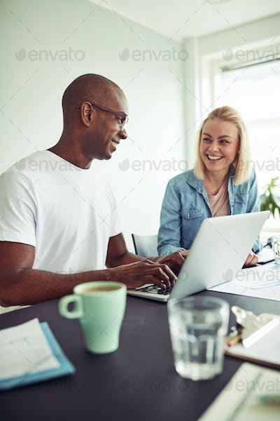 Two diverse coworkers smiling while using a laptop together