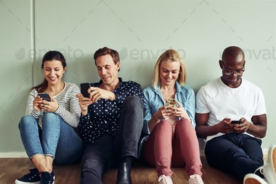 Smiling diverse businesspeople sitting on an office floor using cellphones