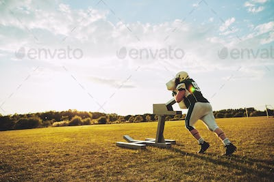 American football player doing tackling drills with a tackle sled