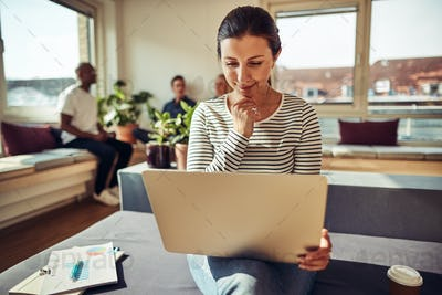 Businesswoman using a laptop with colleagues talking in the background